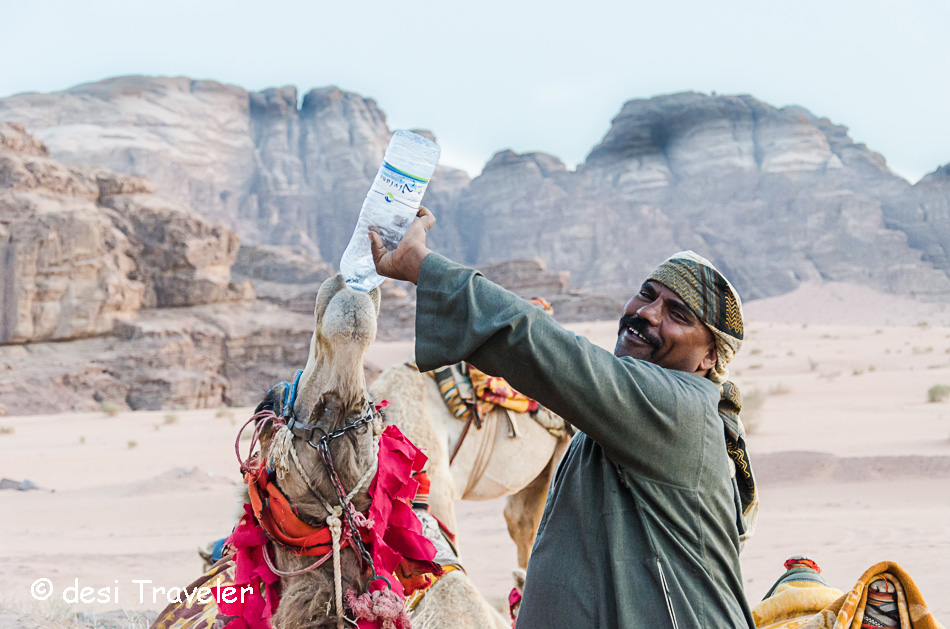 camel herder giving water to camel