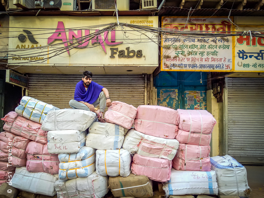 Man sitting on cloth bundles in Chandni Chowk Delhi 6
