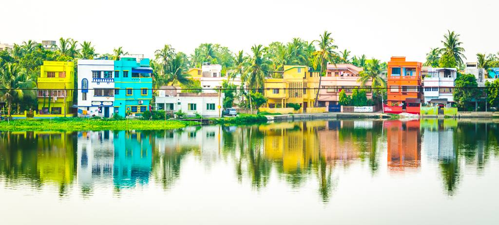 A Pukur or small lake in Kolkata outskirts reflection colorful homes of Indian countryside