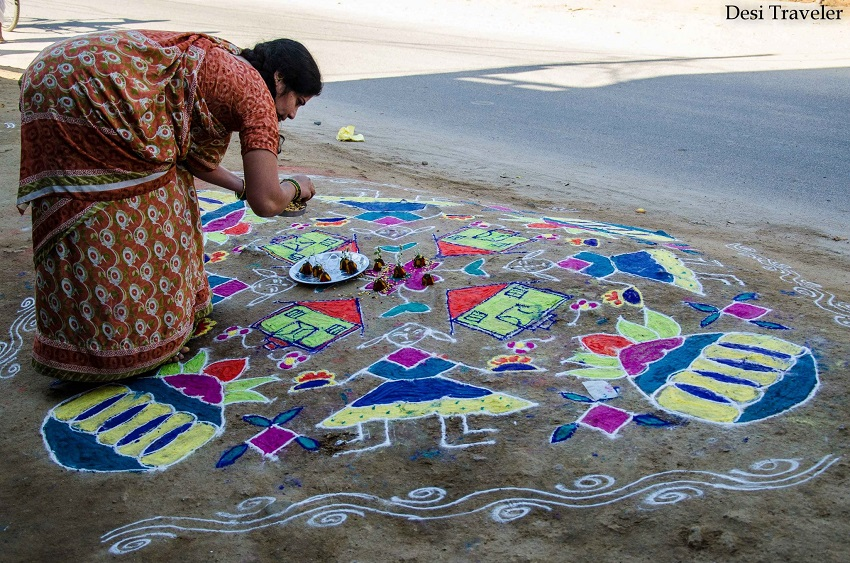 Woman making a traditional Rangoli design Telangana