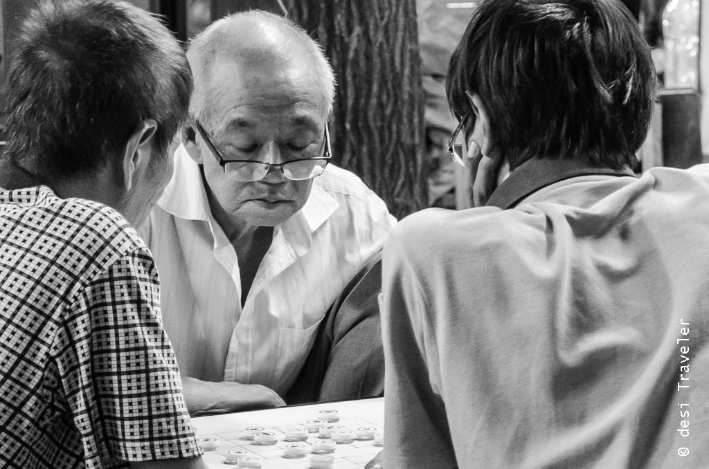 Elders playing board game Chinatown Singapore