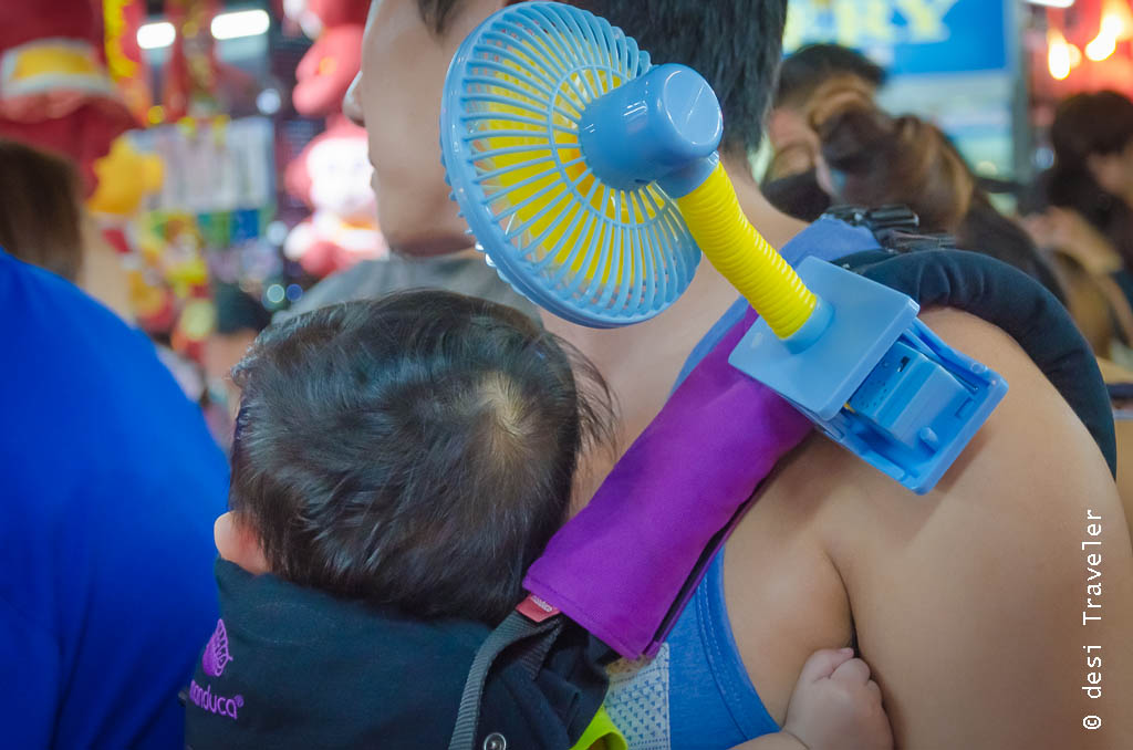 Man holding boy with a portable fan on shoulder