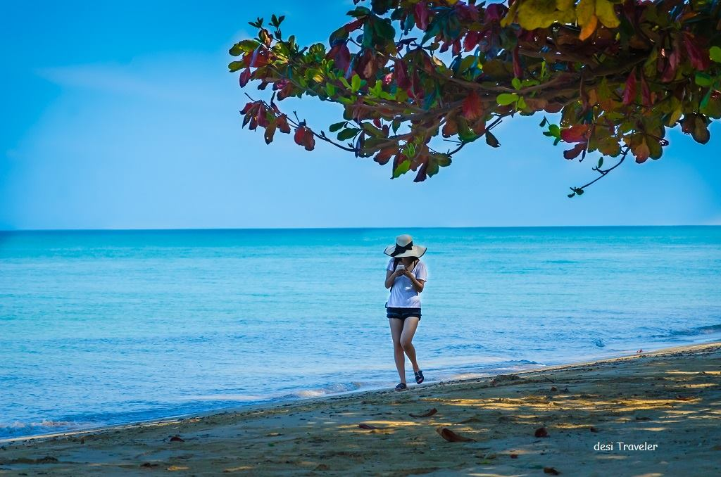 Gilr in hat walking on a beach Thailand