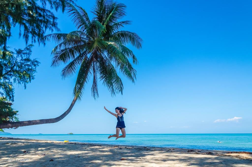 Girl jumping on a beach in Thailand next to coconut tree