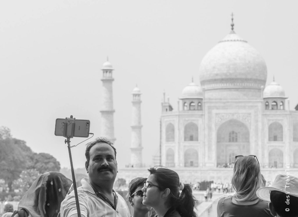 Tourists with selfie stick in front of Taj Mahal